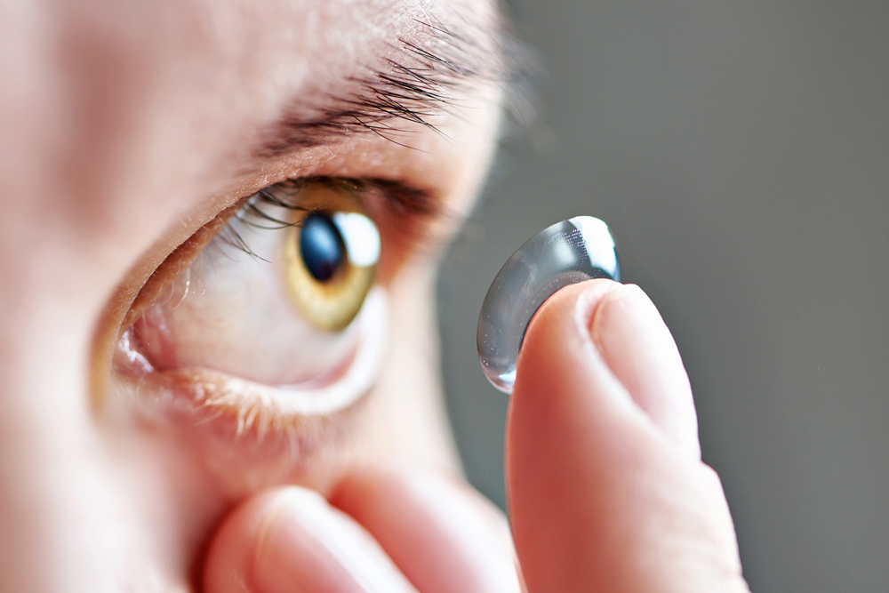 patient applying contact lens